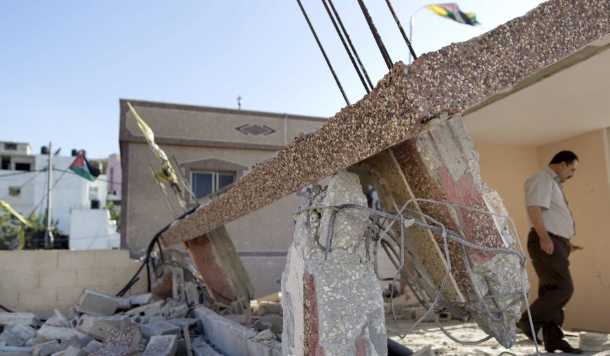 A Palestinian man inspects the damaged house of Anan Abu Habsa, which was demolished by the Israeli army, in the West Bank refugee camp of Qalandia, at the outskirts of Ramallah, Monday, July 4, 2016. (AP Photo/Nasser Nasser)