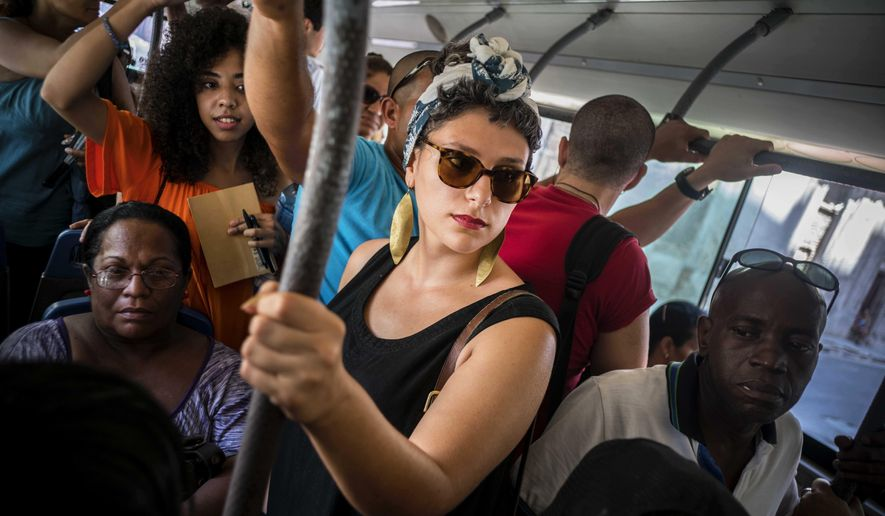 In this June 12, 2016 photo, Cuban American Fontaine Capel, center, travels on a regular bus line in Havana, Cuba. Capel was brought to the island by CubaOne, a new program inspired by the reestablishment of diplomatic and business ties between the U.S. and Cuba. (AP Photo/Ramon Espinosa)