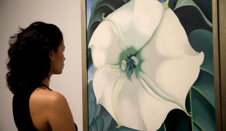 "A Tate Modern representative poses for photographs next to ""Jimson Weed/White Flower No.1"" by American artist Georgia O'Keeffe at a press launch for her retrospective exhibition of over 100 works at the Tate Modern gallery in London, Monday, July 4, 2016. O'Keeffe is one of the iconic American artists of the 20th century, but an exhibition of more than 100 works opening this week at Tate Modern is her biggest-ever show outside the United States. (AP Photo/Matt Dunham)"