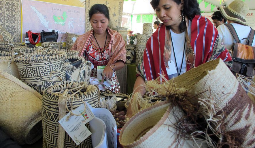 FILE - In this July 11, 2015, file photo, indigenous artisans, who are part of the weaving network Crafts Kalimantan, organize their wares during the 12th annual International Folk Art Market in Santa Fe, N.M. Now in its 13th year, the 2016 International Folk Art Market will feature artists from more than 60 different countries, and organizers say this year marks an opportunity to celebrate differences despite ongoing strife around the globe. (AP Photo/Susan Montoya Bryan, File)