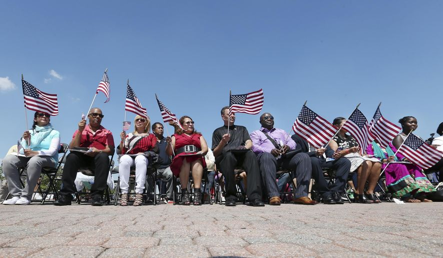 Some of a group of people waves flags during their naturalization ceremony at Liberty State Park, Monday, July 4, 2016, in Jersey City, N.J. Nearly two dozen new U.S. citizens took their oaths of allegiance at the ceremony. The 21 new citizens came from 17 countries: Bangladesh, Bosnia-Herzegovina, Colombia, Dominican Republic, Ecuador, Egypt, El Salvador, Guyana, India, Liberia, Mexico, Nigeria, Pakistan, Peru, Philippines, Poland and Togo. (AP Photo/Mel Evans)