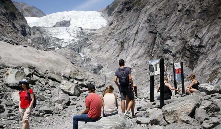 FILE - In this Feb. 6, 2016 file photo, tourist relax at the end of the track at the Franz Josef Glacier in New Zealand. Ski fields are struggling to open and winter electricity consumption is down in New Zealand after the first six months of 2016 proved to be the hottest start to a year that scientists have ever recorded. Temperatures in the South Pacific nation were 1.4 degrees Celsius (2.5 Fahrenheit) above the long-term average for the first half of the year, according to the government-funded National Institute of Water and Atmospheric Research.(AP Photo/Nick Perry)