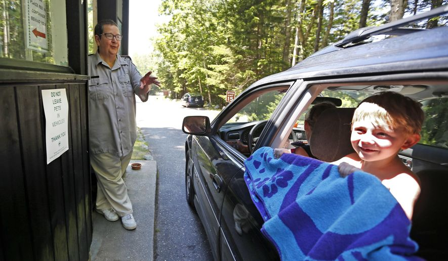 In this July 1, 2016 photo, Sarah Crosby speaks to a visitor heading to the beach at Reid State Park in Georgetown, Maine. Crosby has worked the forested entryway to Maine's oldest state-owned beach since 1972. (AP Photo/Robert F. Bukaty)