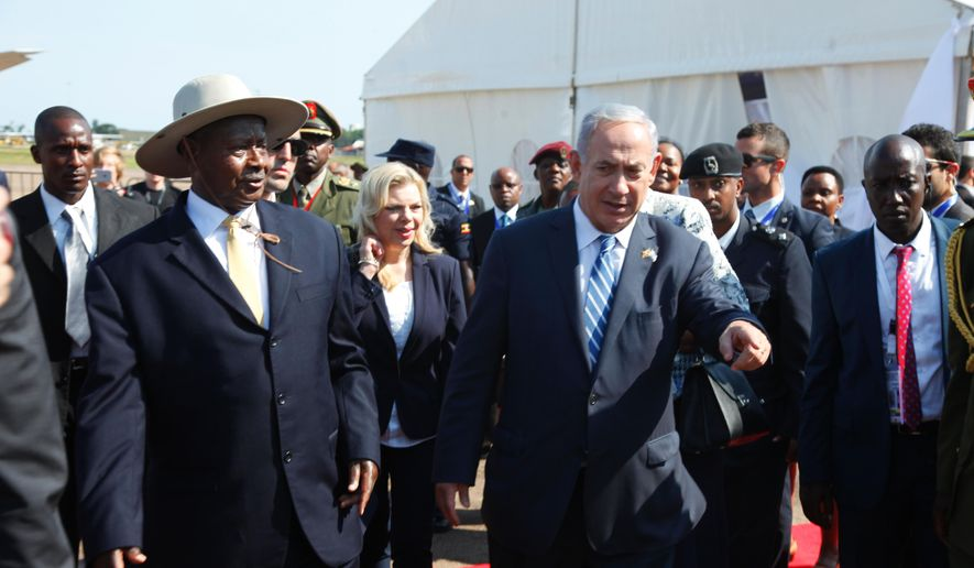 Israeli Prime Minister, Benjamin Netanyahu, right, is greeted by Ugandan President, Yoweri Museveni, on this arrival in at Entebbe airport Uganda, Monday, July 4, 2016. Netanyahu is on a four-nation Africa tour of Uganda, Kenya, Rwanda and Ethiopia. (AP Photo/Stephen Wandera)
