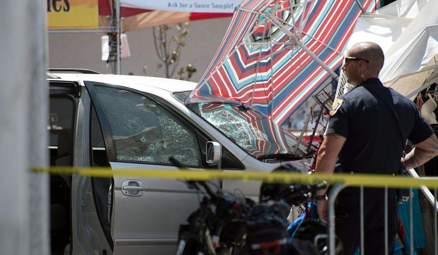 A Reno police officer stands guard at the scene after a minivan crashed into a vendor's tent at the Biggest Little City Wing Fest in downtown Reno, Nev. Festival goers there thought they were hearing fireworks when police opened fire and killed a man in the minivan that crashed at the downtown chicken wing cook-off. (Michael Higdon/The Reno Gazette-Journal via AP)