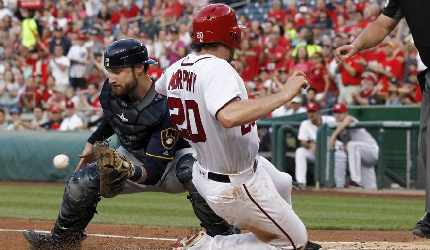Milwaukee Brewers catcher Jonathan Lucroy waits for the throw as Washington Nationals' Daniel Murphy (20) slides safely into home on a single by Anthony Rendon during the second inning of a baseball game at Nationals Park, Tuesday, July 5, 2016, in Washington. (AP Photo/Alex Brandon)
