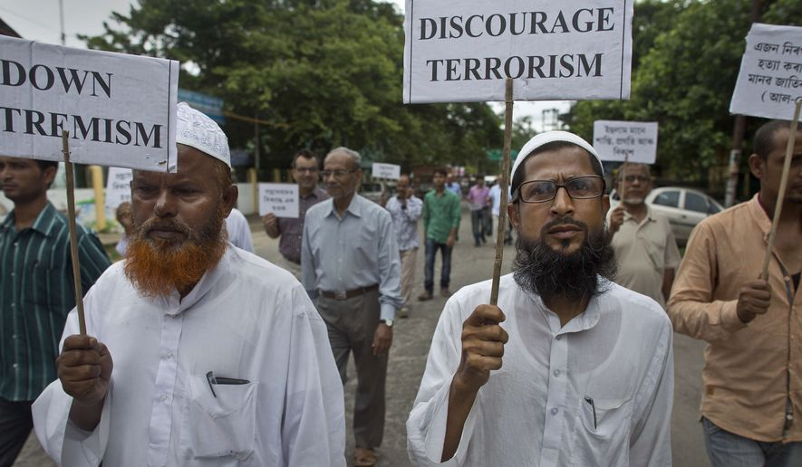 Indian Muslims holding placards condemning the weekend militant attacks in Bangladesh walk in a procession in Gauhati, India, Tuesday, July 5, 2016. (AP Photo/ Anupam Nath)