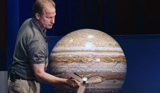 Juno Project Manager Rick Nybakken holds a model of the Juno spacecraft as he discusses the orbit it will take around Jupiter during a briefing at the Jet Propulsion Laboratory in Pasadena, California, on Monday. (Associated Press)