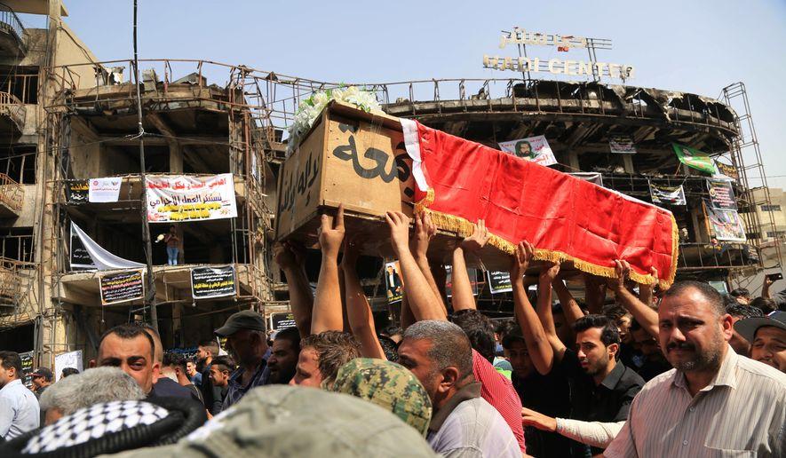 Mourners carry the Iraqi flag-draped coffin of, Akram Hadi, 24, in a Sunday massive truck bomb attack in the Karada neighborhood of Baghdad, Iraq, Tuesday, July 5, 2016. (AP Photo/Karim Kadim)