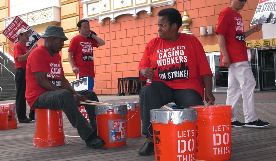 Striking union members bang on plastic buckets outside the trump Taj Mahal casino in Atlantic City N.J. during a strike Tuesday July 5, 2016. Presumptive Democratic presidential nominee Hillary Clinton is to visit Atlantic City on Wednesday to bash Donald Trump's record of running casinos here in the 1908s and 1990s, but the presumptive Republican presidential nominee hasn't owned the Taj Mahal for years; it now belongs to his friend and fellow billionaire Carl Icahn. (AP Photo/Wayne Parry)