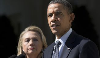 In this Sept. 12, 2012, file photo, then-Secretary of State Hillary Clinton listens at left, as President Barack Obama speaks in the Rose Garden of the White House in Washington, on the death of U.S. ambassador to Libya Christopher Stevens. (AP Photo/Evan Vucci) ** FILE **