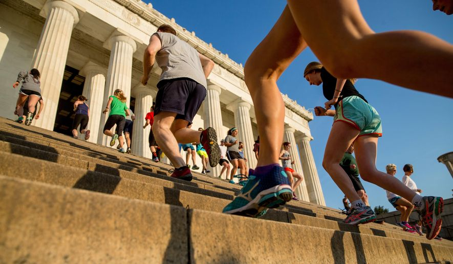 "In this May 25, 2016 photo, members of the running group ""November Project"" run up and down the stairs of the Lincoln Memorial, in Washington. Fitness buffs around the country are bringing the 'take the stairs' advice to a whole new level as noteworthy landmarks have become unlikely, yet popular new workout sites. (AP Photo/Andrew Harnik)"
