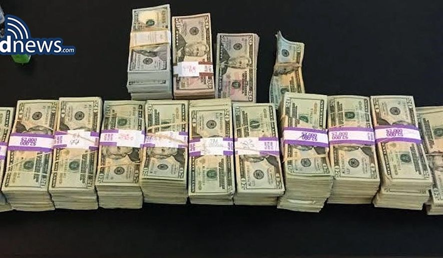 "In this photo released July 5, 2016 by the Boston Police Department, stacks of money totaling about $187,000 that were left in a taxi are displayed in Boston. Boston police said cab driver Raymond ""Buzzy"" MacCausland picked up a rider in Boston on Saturday who left a backpack containing the money in the taxi. After being unable to locate the man, MacCausland drove to police headquarters to turn in the cash. The unidentified rider was reunited with his money, which turned out had been inherited. MacCausland received a $100 reward. (Boston Police Department via AP)"