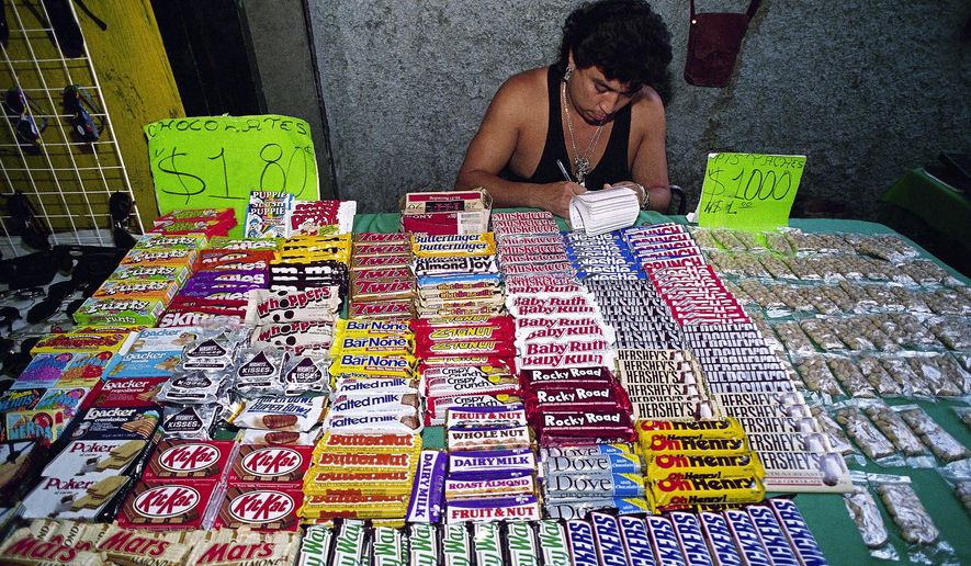 FILE - In this Nov. 16, 1993, file photo, a street vendor sells chocolates in Mexico City. A study published Tuesday, July 5, 2016, shows that Mexico's 8-percent tax on high-calorie snacks has been successful in reducing junk food purchases, but only by a small amount and only among poor and middle-class households. (AP Photo/Damian Dovarganes, File)