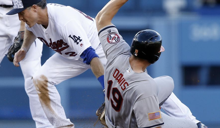 Baltimore Orioles' Chris Davis (19) advances to second, as Los Angeles Dodgers second baseman Chase Utley, left, applies the late tag on a throw from third, after fly ball to right, during the second inning of a baseball game in Los Angeles, Monday, July 4, 2016. (AP Photo/Alex Gallardo)