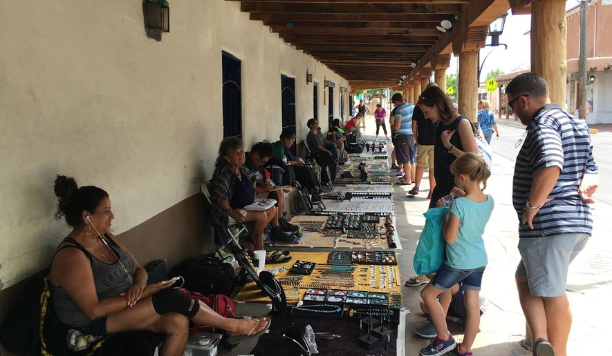"In this June 22, 2016 photo, tourists line up outside the plaza in Albuquerque's Old Town to buy jewelry from American Indian vendors. New Mexico officials said Tuesday, July 5, 2016, the state saw ""record-breaking"" tourism for the fourth year in a row in 2015. (AP Photo/Russell Contreras)"