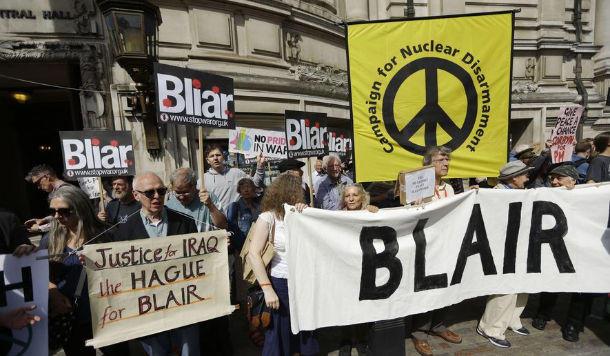 Protesters hold placards outside the Queen Elizabeth II Conference Centre in London, shortly before the publication of the Chilcot report into the Iraq war, Wednesday, July 6, 2016. (AP Photo/Matt Dunham)