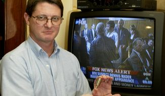 """Sam Kimery holds his """"Fox Blocker,"""" a device that blocks the reception of the Fox News cable channel, seen on television at rear, at his home in Tulsa, Oklahoma. Mr. Kimery contends Fox News' top-level management dictates a conservative journalistic bias, that inaccuracies are never retracted, and what winds up on the air is more opinion than news. (Associated Press)"""