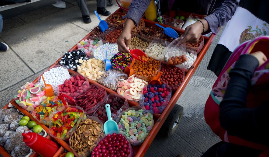 A street vendor sells sweet snacks in Mexico City, Tuesday, July 5, 2016. A study published on Tuesday shows that Mexico's 8-percent tax on high-calorie snacks has been successful in reducing junk food purchases, but only by a small amount and only among poor and middle-class households. (AP Photo/Eduardo Verdugo)