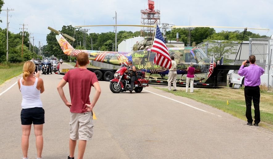 "People watch as the ""Take Me Home Huey"" exhibit by contemporary artist and Kalamazoo native Steve Maloney arrives at the Air Zoo aerospace & science museum on its East campus in Kalamazoo, Tuesday, July 5, 2016. ""Take Me Home Huey"" is a sculptural installation created by Maloney from the remains of an historic U.S. Army Huey helicopter that was shot down in 1969 during a medical rescue in Vietnam. The work will be displayed at the Air Zoo's East Campus 3101 E. Milham Rd in Kalamazoo. (Mark Bugnaski/Kalamazoo Gazette-Mlive.com via AP)"