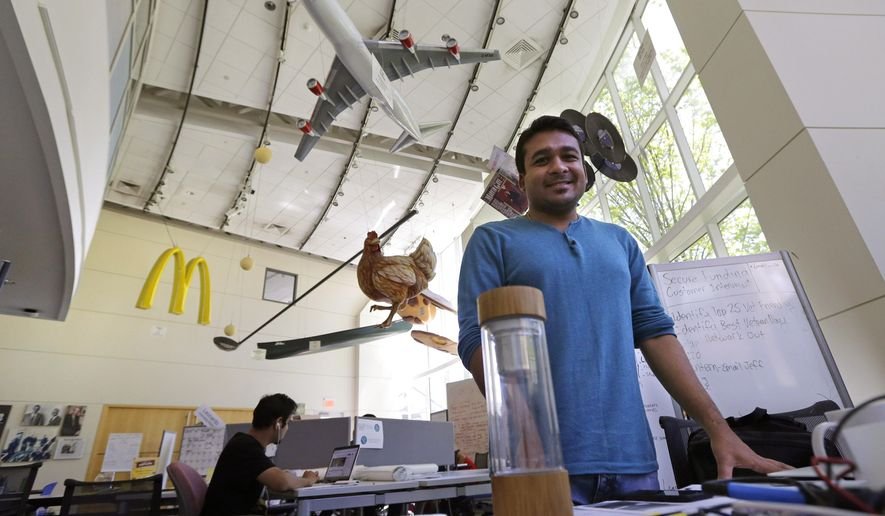 In this Thursday, June 30, 2016 photograph, Babson College graduate school alumnus Abhinav Sureka, of Mumbai, India, poses in his work space at the college in Wellesley, Mass. Some U.S. colleges are starting programs to help their alumni get visas through what critics say is a legal loophole. Foreign grads who want to stay and start a business typically apply for one of the 85,000 H-1B visas that the U.S. gives out each year. But college employees are exempt from that cap, so schools like UMass, Babson and CUNY have launched programs to hire alumni and foreign entrepreneurs and help them grow their businesses here. (AP Photo/Charles Krupa)