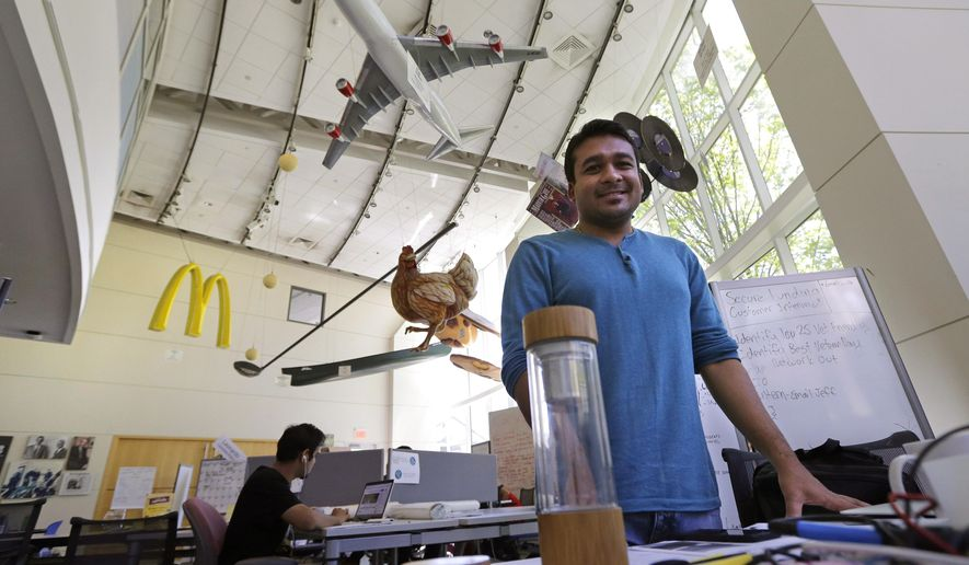In this Thursday, June 30, 2016, file photograph, Babson College graduate school alumnus Abhinav Sureka, of Mumbai, India, poses in his work space at the college in Wellesley, Mass. Some U.S. colleges are starting programs to help their alumni get visas through what critics say is a legal loophole. Foreign grads who want to stay and start a business typically apply for one of the 85,000 H-1B visas that the U.S. gives out each year. But college employees are exempt from that cap, so schools like UMass, Babson and CUNY have launched programs to hire alumni and foreign entrepreneurs and help them grow their businesses here. (AP Photo/Charles Krupa) ** FILE **