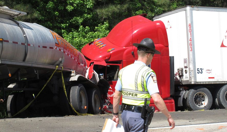 File- This April 22, 2015, file photo shows a Georgia state trooper working the scene of a deadly crash in which five people died and three others were injured in Ellabelle, Ga.  A southeast Georgia prosecutor said Wednesday, July 6, 2016,  that he has dropped the criminal case against a trucking company charged in a fiery interstate crash last year that killed five nursing students. District Attorney Tom Durden of Georgia's Atlantic Judicial Circuit said he made the decision after Total Transportation of Mississippi agreed to spend $200,000 setting up a nonprofit group offering nursing students financial aid. A grand jury indicted the company in June on charges of vehicular homicide and other crimes related to the deadly crash.   (AP Photo/Russ Bynum, File)