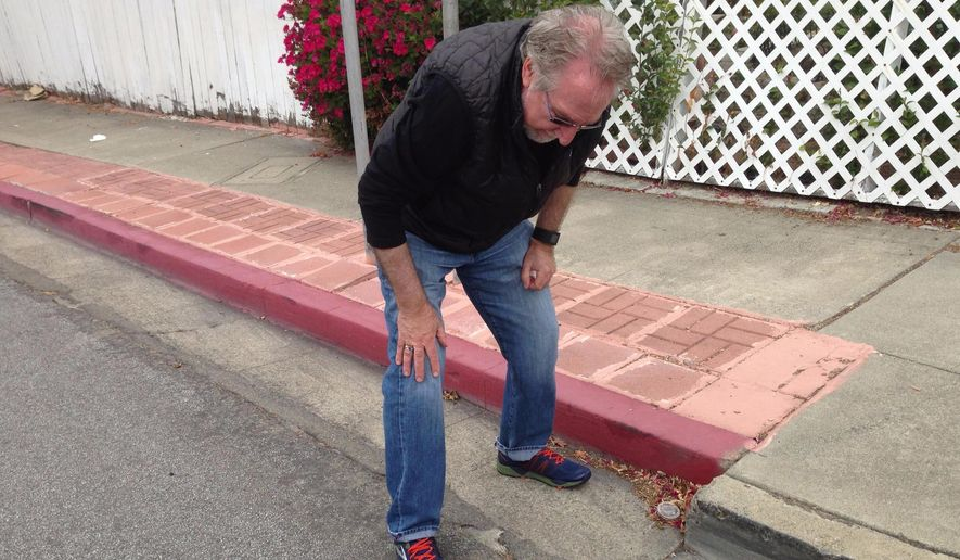 U.S. Geological Survey research geologist David Schwartz looks at a curb has been pulled apart over the decades by the powerful seismic forces of the Hayward fault on June 7, 2016 in Hayward, Calif. Since at least the 1970s, scientists have painstakingly photographed the curb as the Hayward fault pushed it farther and farther out of alignment. (Rong-Gong Lin II/Los Angeles Times via AP)