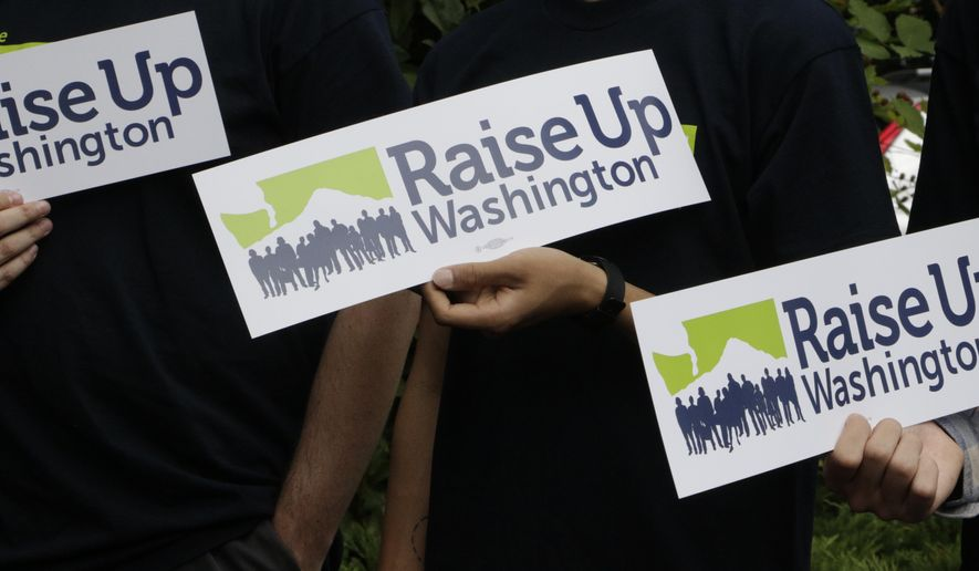 Supporters of raising the state minimum wage hold signs at a news conference, on Wednesday, July 6, 2016, in Olympia, Wash. Initiative 1433 seeks to incrementally increase the state's rate over the next four years to $13.50 an hour and to provide paid sick leave to employees who don't currently have it.  (AP Photo/Rachel La Corte)