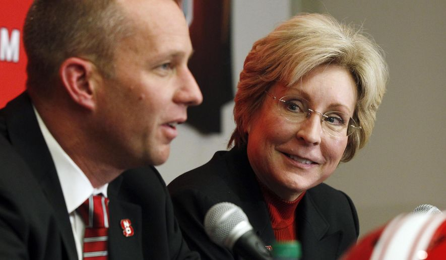 FILE - In this Dec. 2, 2012, file photo, North Carolina State athletic director Debbie Yow, right, listens as football head coach Dave Doeren speaks during a news conference in Raleigh, N.C. Yow has guided the Wolfpack within a step or two of her stated goal of building a national top-25 program. (Ethan Hyman/The News & Observer, File) MANDATORY CREDIT