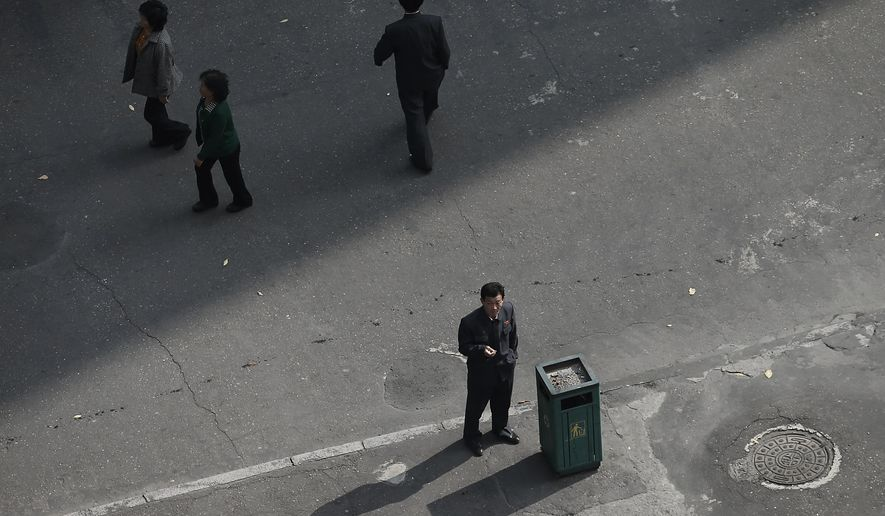 In this Oct. 25, 2014, file photo, a North Korean man smokes a cigarette on the sidewalk in downtown Pyongyang, North Korea. North Korea, one of the last bastions of free, unhindered smoking, a country where just about every adult male can and does light up almost anywhere he pleases, is now officially trying to get its people to kick the habit. (AP Photo/Wong Maye-E, File)