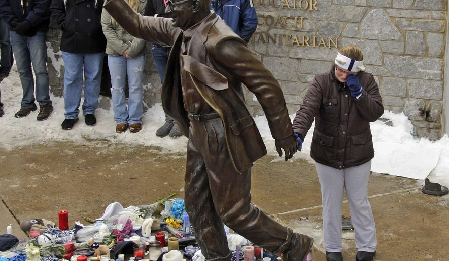 FILE - In this Jan. 22, 2012,  file photo, a woman pays her respects at a statue of former Penn State football coach Joe Paterno outside Beaver Stadium on the Penn State University campus in State College, Pa. More than 200 former Penn State football players are petitioning university leaders to return the bronze statue of Paterno that stood outside the school's football stadium. The statue of the late football coach was removed in 2012. The players sent a letter Tuesday, July 5, 2016, to the board of trustees and Penn State President Eric Barron calling for the statue's return. (AP Photo/Gene J. Puskar, File)