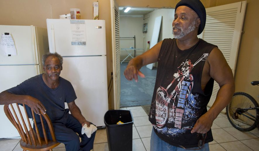 David Solomon, 60, left, and Calvin Wilson, 56, right, say they lived with Alton Sterling at the Living Waters Outreach Ministry Drop-In Center, and don't believe he carried a gun, on Tuesday, July 5, 2016, in Baton Rouge. Sterling was fatally shot during an altercation with Baton Rouge Police in the early morning hours of Tuesday, outside a Baton Rouge convenience store. (Travis Spradling/The Advocate via AP)