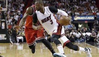 FILE - In this April 7, 2016, file photo, Miami Heat guard Dwyane Wade (3) drives around Chicago Bulls guard Jimmy Butler during an NBA basketball game in Miami. A person with knowledge of the situation tells The Associated Press that Wade has decided to leave the Heat and sign with the Bulls. Wade made the decision Wednesday night, July 6, according to the person who spoke on condition of anonymity because nothing can be finalized before Thursday. (AP Photo/Alan Diaz, File)