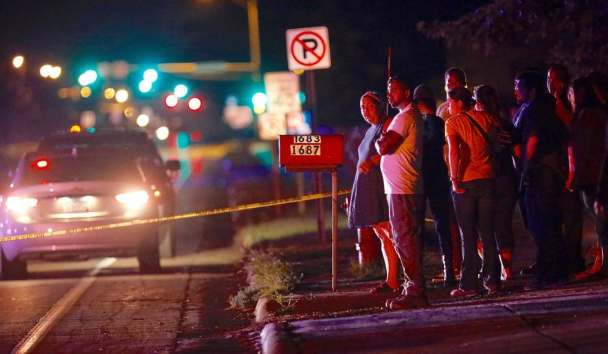 A crowd gathers at the scene of a shooting of a man involving a St. Anthony Police officer on Wednesday, July 6, 2016, in Falcon Heights, Minn. Police in Minnesota say a man has been taken to a hospital in unknown condition after being shot by an officer while inside a car with a woman and a child. St. Anthony Police interim police chief Jon Mangseth told reporters at a news conference that the incident began when an officer from his agency initiated a traffic stop around 9 p.m. Wednesday in Falcon Heights, a St. Paul suburb. (Leila Navidi/Star Tribune via AP)