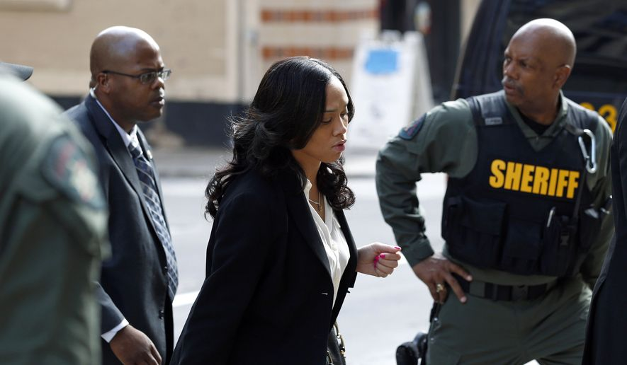 Baltimore state's attorney Marilyn Mosby, center, arrives at a courthouse before opening statements in the trial of Lt. Brian Rice, one of six members of the Baltimore Police Department charged in connection to the death of Freddie Gray, in Baltimore, Thursday, July 7, 2016. (AP Photo/Patrick Semansky)