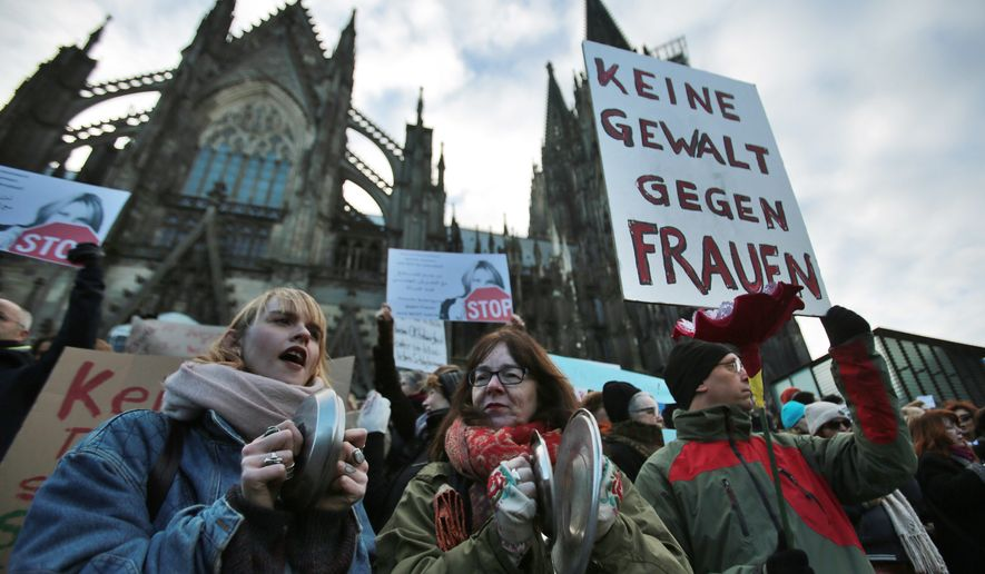 "In this Jan. 9, 2016, file photo people demonstrate against racism and sexism in Cologne, Germany in the aftermath of a string of New Year's Eve sexual assaults and robberies. German lawmakers debated a bill Thursday, July 7, 2016, that will make it easier for victims of sex crimes to file criminal complaints if they rejected their attacker's advances with a clear ""no."" Poster reads ""No violence against women."" (Oliver Berg/dpa via AP, file) **FILE**"