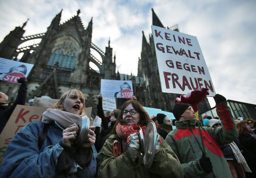 """In this Jan. 9, 2016, file photo people demonstrate against racism and sexism in Cologne, Germany in the aftermath of a string of New Year's Eve sexual assaults and robberies. German lawmakers debated a bill Thursday, July 7, 2016, that will make it easier for victims of sex crimes to file criminal complaints if they rejected their attacker's advances with a clear """"no."""" Poster reads """"No violence against women."""" (Oliver Berg/dpa via AP, file) **FILE**"""