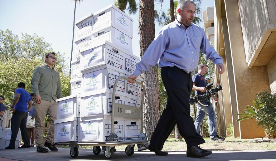 Arizona State Elections Director Eric Spencer, right, brings boxes to the elections office at the Arizona Capitol, Thursday, July 7, 2016, in Phoenix, from the Arizona Healthy Working Families Initiative group with more than 270,000 signatures the organization gathered. The group hopes to qualify a measure for the November ballot to raise the state's minimum wage to $12 an hour by 2020 and provide earned sick days to workers. (AP Photo/Ross D. Franklin)