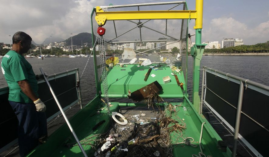 FILE - In this Jan. 6, 2016 file photo, a worker stands next to trash collected by a garbage-collecting barge in Guanabara Bay in Rio de Janeiro, Brazil. The head of World Sailing said in an interview on Wednesday, July 6, 2016 that the boats will be critical in keeping the bay safe and fair for Olympic racing. (AP Photo/Silvia Izquierdo, File)