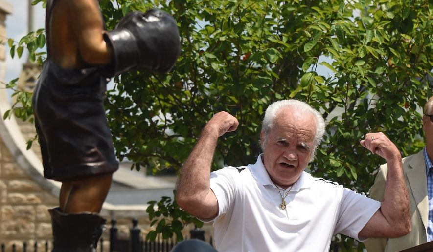 John Robertson flexes into a pose while looking at statue just unveiled at John Robertson Park in Altoona, Pa., Wednesday, July 6, 2016. About 20 men who trained with Robertson showed up for the unveiling of a statue to honor their mentor in a park named for him at the eastern end of the Seventh Street Bridge, across from the site of Robertson's childhood home. (J.D. Cavrich/Altoona Mirror via AP)