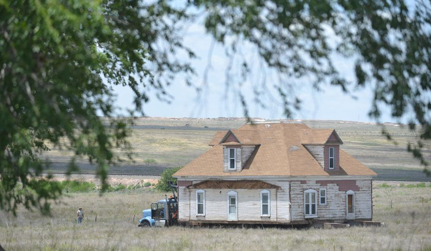 In a Monday, June 27, 2016 photo, house owner Paul Burks and crews with McDowell House and Structure Moving haul a historic 1900s home across an 80-acre pasture outside Canyon to its new location off Highway 60. The historic house was the home of W.F. Heller, a Civil War veteran and the first to farm in the area successfully in the late 1800s.  (Michael Schumacher/Amarillo Globe-News via AP)