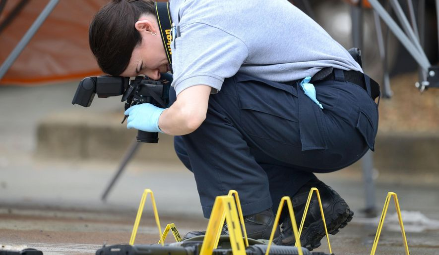 A law enforcement agent photographs the scene of a multiple shooting in Bristol, Tenn., on Thursday, July 7, 2016.  Police say multiple people have been injured and one person was taken into custody after a man opened fire on motorists traveling along a parkway in East Tennessee. Bristol police say the incident happend early Thursday in the city along the Virginia border. (David Crigger/The Bristol Herald-Courier via AP)