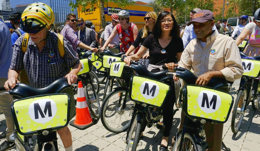 People prepare to test ride bikes in Grand Park near Los Angeles City Hall Thursday, June 7, 2016. The city is rolling out a bicycle sharing program offering bikes for rent from dozens of locations downtown. The agreement with the county's Metropolitan Transportation Authority creates up to 65 bike-sharing stations. Users can pick up a bike from a kiosk, hop on, and then leave it near their destination for someone else to use. (AP Photo/Richard Vogel)