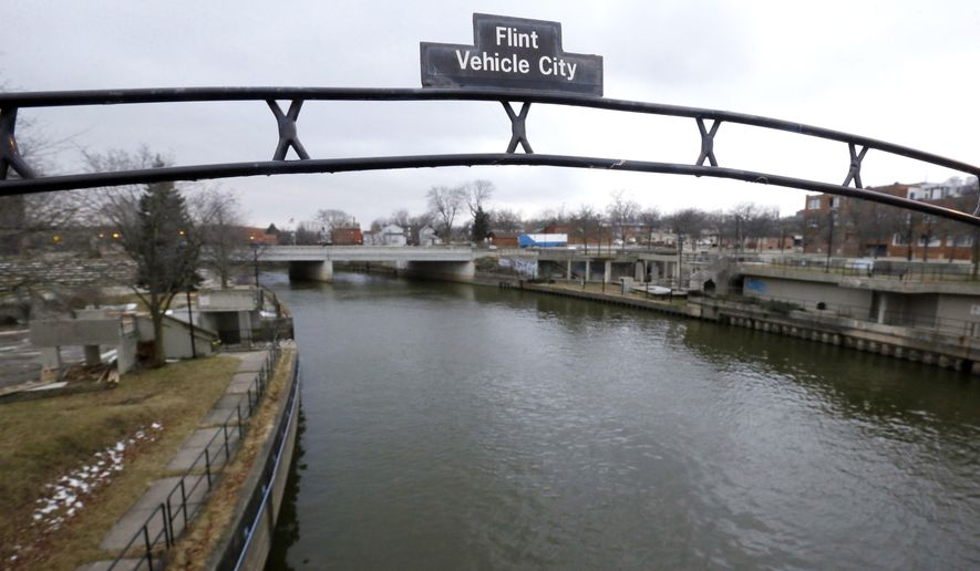 FILE - This Jan. 26, 2016, file photo shows a sign over the Flint River noting Flint, Mich., as Vehicle City. The U.S. Environmental Protection Agency says states are taking action to address the risk of lead in drinking water but more needs to be done to share key information with the public. In letters to state officials, Thursday, July 7, EPA urged states to post individual lead sampling results on public websites. That practice allows residents to see which homes and buildings have been tested and what level of lead was identified. (AP Photo/Carlos Osorio, File)