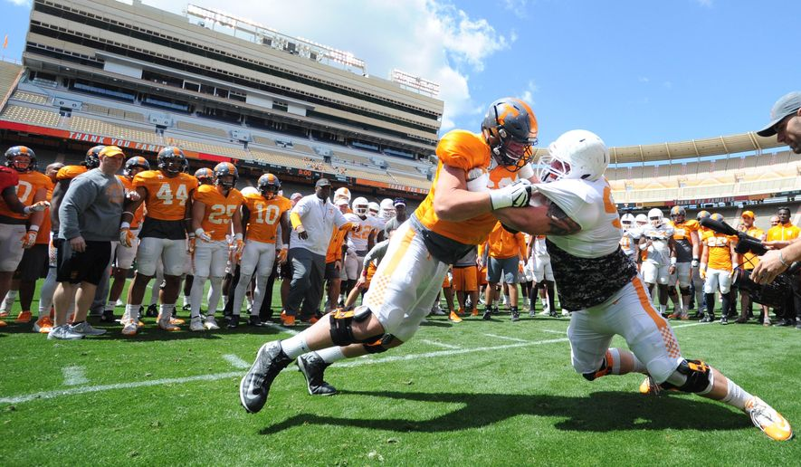 FILE - In this April 2, 2016, file phot, Tennessee offensive lineman Austin Sanders, left, and defensive lineman Danny O'Brien battle during spring NCAA college football practice at Neyland Stadium in Knoxville, Tenn. Power Five conference commissioners want to change NCAA rules to give college athletes more time away from team activities, including no longer counting travel as an off day, a mandatory seven-day break after the season and an additional 14 off days from athletic activity during the academic year. The agreement in concept was announced Thursday, July 7, 2106, by the Atlantic Coast Conference, Big Ten, Big 12, Pac-12 and Southeastern Conference. (Adam Lau/Knoxville News Sentinel via AP, File) MANDATORY CREDIT