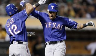 FILE - In this May 17, 2016, file photo, Texas Rangers' Ian Desmond, right, celebrates with Rougned Odor (12) after hitting a two-run home run off Oakland Athletics' Ryan Madson during the ninth inning of a baseball game in Oakland, Calif. Desmond wasn't the biggest name on the free agent market, not by a longshot. But his big first half has helped Texas take a commanding lead in the AL West, and he's been one of the most successful new acquisitions in baseball so far in 2016. (AP Photo/Ben Margot, File)
