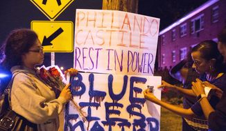 Protester's hang signs on a post near the scene of Philando Castile's shooting in Falcon Heights, Minn., Thursday, July 7, 2016. Castile was shot in a car Wednesday night in the largely middle-class St. Paul suburb of Falcon Heights. Police have said the incident began when an officer initiated a traffic stop in suburban Falcon Heights but have not further explained what led to the shooting. .(Leila Navidi/Star Tribune via AP) ** FILE **