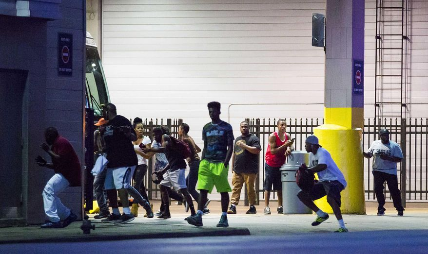 Bystanders run for cover after shots fired at a Black Live Matter rally in downtown Dallas on Thursday, July 7, 2016. Dallas protestors rallied in the aftermath of the killing of Alton Sterling by police officers in Baton Rouge, La. and Philando Castile, who was killed by police less than 48 hours later in Minnesota. (Smiley N. Pool/The Dallas Morning News)