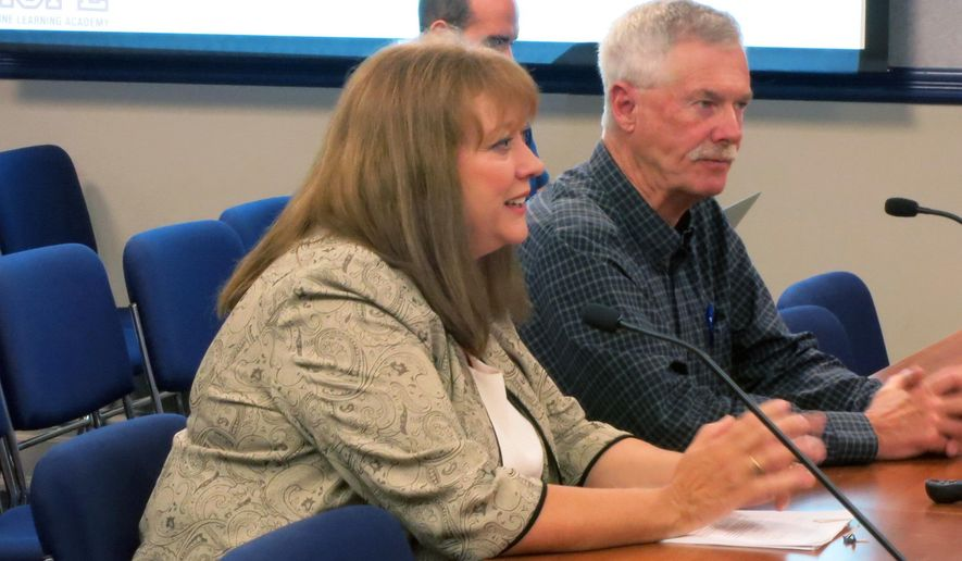 Darci Mohr, front, superintendent of the South Routt County School District, makes a point while Tim Corrigan, a county commissioner from Routt County, Colo., listens in during a meeting of the Colorado Board of Education Thursday, July 7, 2016, in Denver. The tiny school district caught up in a giant coal company's financial woes got a million-dollar bailout Thursday with a vote by the Colorado board of education to empty its emergency fund to help. (AP Photo/Donna Bryson)